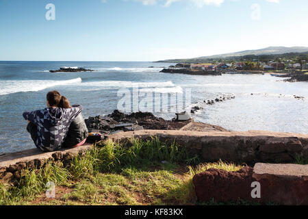EASTER ISLAND, CHILE, Isla de Pascua, Rapa Nui, a couple sits and watches the surf come in near Hanga Roa - Stock Photo