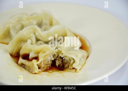 Japanese boiled Dumplings dressing soy sauce on plate - Stock Photo
