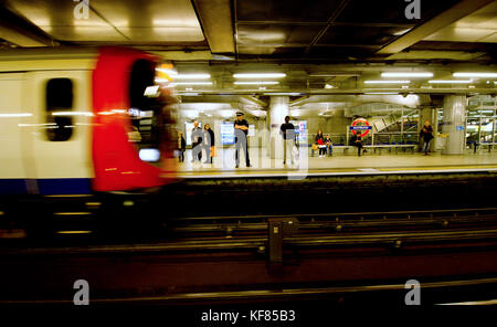 London, England, UK. Police officer on the platform of Westminster underground station as a train arrives - Stock Photo