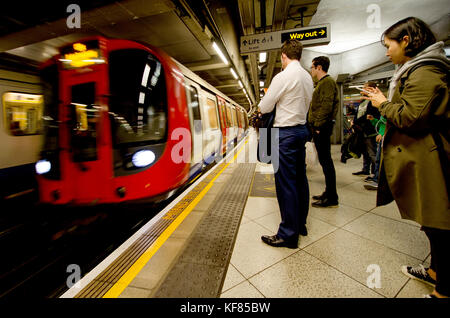 London, England, UK. People on the platform of Westminster underground station as a train arrives - Stock Photo