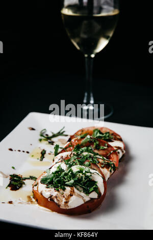 Fresh italian caprese salad with mozzarella cheese, tomatoes and basil on a white plate and black background - Stock Photo