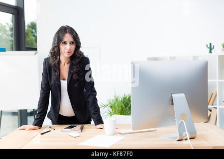 pregnant businesswoman looking at computer - Stock Photo