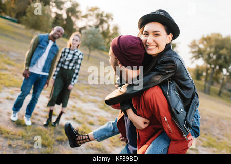 couple piggybacking in park - Stock Photo