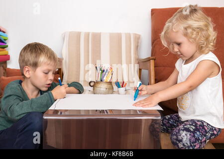 Boy and girl drawing on paper having creative time at home - Stock Photo