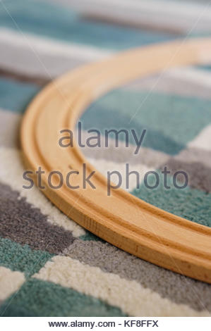 Close up of a wooden toy train track on a carpet - Stock Photo
