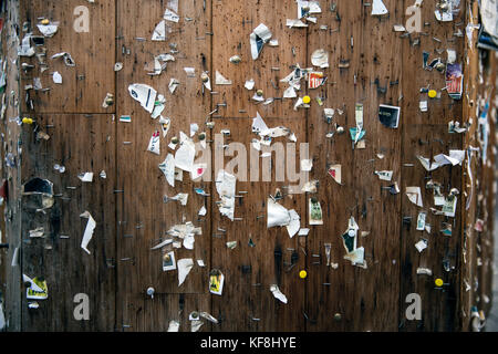 USA, Oregon, Ashland, detail of staples and torn paper advertisements on a message board in the town square in downtown - Stock Photo