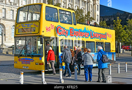 Liverpool open top City Explorer sightseeing tour bus picking up passengers at bus stop on the Pier Head Waterfront - Stock Photo