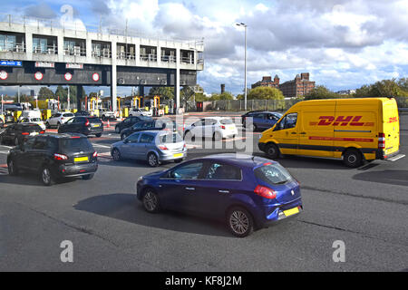 Short queues of traffic at toll booths on Wallasey side of Kingsway tunnel passing under River Mersey linking with - Stock Photo