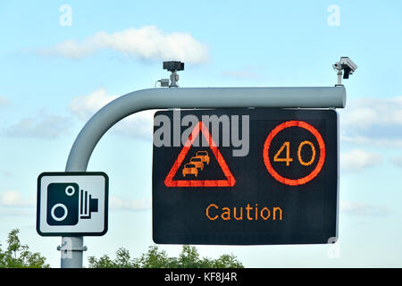Single panel M25 motorway sign above lane one only, variable speed limit & short caution message complete with CCTV - Stock Photo