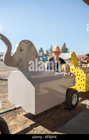 USA, Oregon, Bend, a mom and daughter on the tractor ride at the annual pumpkin patch located in Terrebone near - Stock Photo