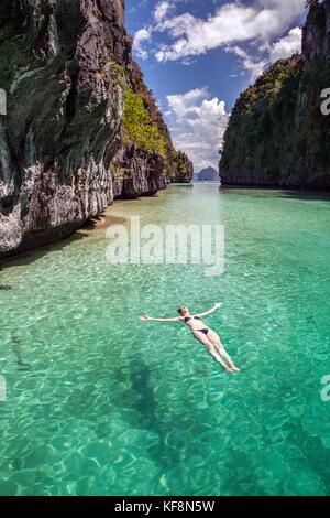 PHILIPPINES, Palawan, El Nido, Miniloc Island, a woman floats on her back in Big Lagoon on Miniloc Island located - Stock Photo