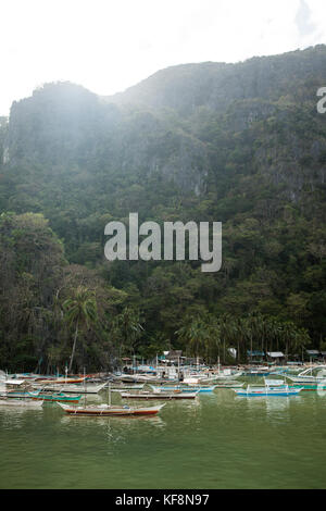 PHILIPPINES, Palawan, El Nido, fishing boats are anchored below the jungle in the town of El Nido, located in Bacuit - Stock Photo
