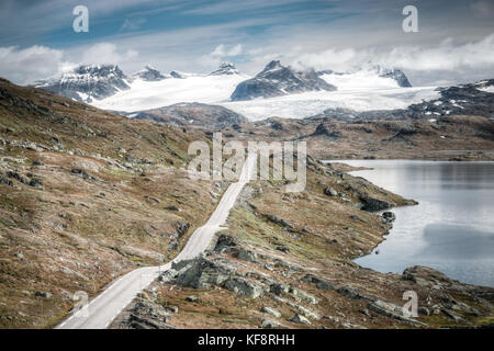 Vintage retro effect filtered hipster style travel image of mountain road leading to spectacular glaciers and lakes. - Stock Photo