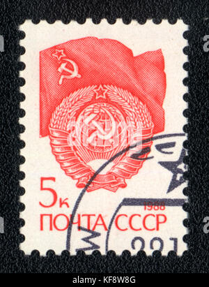 A postage stamp printed in USSR shows Red State Emblem and red flag of the Soviet Union ,circa 1988 - Stock Photo