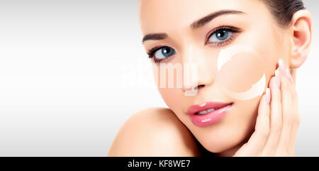 Young woman's face, antiaging concept, grey background. - Stock Photo