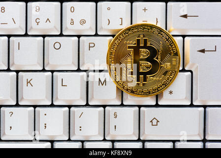 Golden color bitcoin on a computer keyboard - Stock Photo