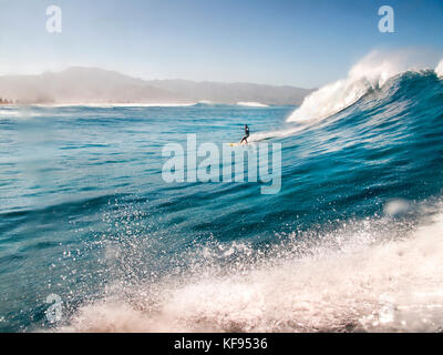 woman tow surfing on the north shore of hawaii - Stock Photo