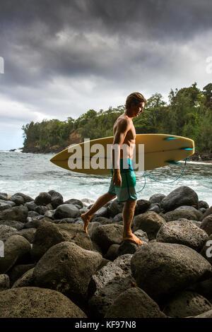 USA, Hawaii, The Big Island, portrait of a surfer on a rocky shoreline at the Hakalau River mouth, North of Hilo - Stock Photo