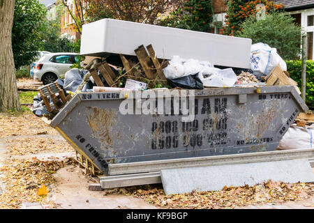 A full waste skip with an old mattress on top of it. - Stock Photo