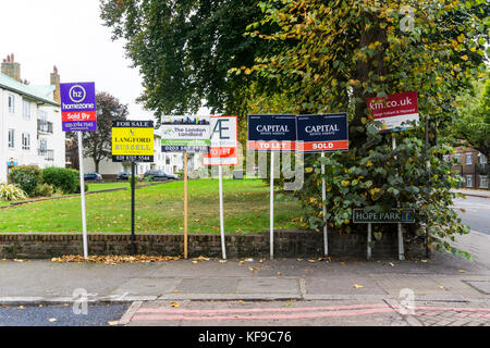 Multiple Sold, For Sale and To Let estate agents' boards outside a block of residential flats in south London. - Stock Photo