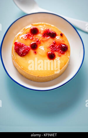 Lemon tart with red fruits on blue surface - Stock Photo