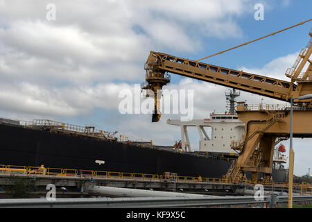 Coal being loaded into the hold of the ship at the dockside at Newcastle, New South Wales,Australia.Ready for transporting - Stock Photo