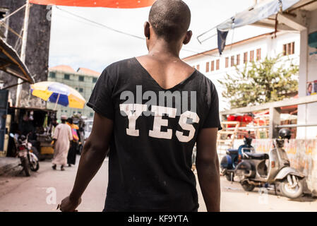 African man walking on a market street photographed from behind wearing a black T-shirt with YES written in white - Stock Photo