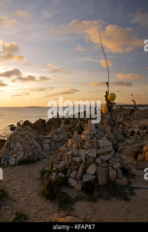 Sunset with stone piles at Ses Illetes beach with Es Vedrá and Ibiza islands in the background from Formentera (Balearic - Stock Photo