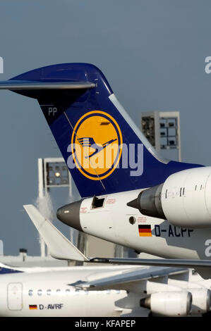 CRJ tail with logo, winglets and engines passing Terminal1 with a Lufthansa BAE 146 RJ-85 behind - Stock Photo