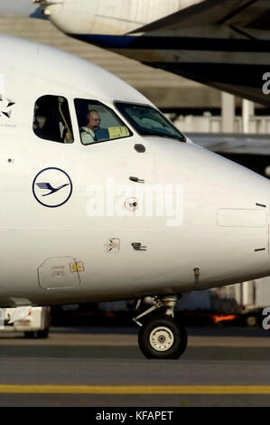 nose-undercarriage and nose with logo taxiing with co-pilot visible through the windshields - Stock Photo