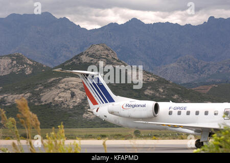tail and Rolls-Royce AE 3007A engine of an Air France - Regional Airlines Embraer ERJ-145 with hills behind - Stock Photo