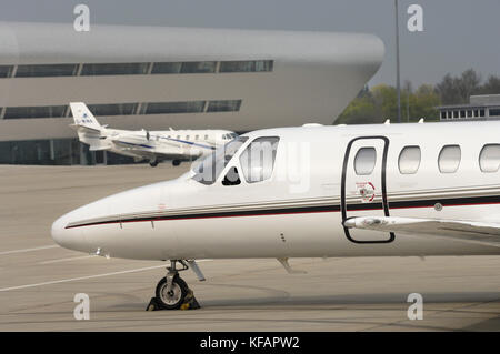 nose of a NetJets Europe Cessna 550 Citation Bravo with a Cessna Citation 560XL parked and the TAG Aviation terminal - Stock Photo
