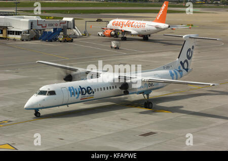 a Flybe Bombardier DHC-8 Dash 8-400 Q400 taxiing with an easyJet Airbus A319-100 parked behind - Stock Photo
