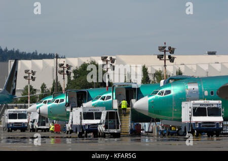 row of noses of Boeing 737 Next Generation parked with airport vehicles outside the production factory - Stock Photo