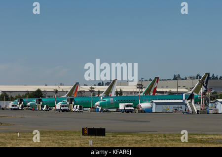 a row of four Boeing 737 Next Generation parked outside the production factory - Stock Photo