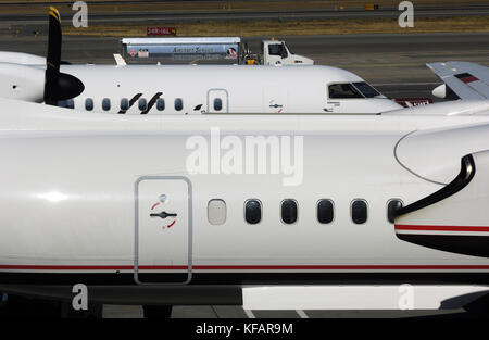 fuselages of Horizon Air Bombardier DHC-8 Dash 8-400 Q400s with an ASIG refuelling bowser behind - Stock Photo