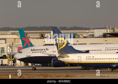 tail-fins of Ryanair Boeing 737-800 and First Choice Airawys 757-200 parked with nose of Monarch Airlines Airbus - Stock Photo