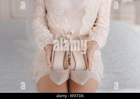 Bride puts on shoes. wedding details at the bride's fees - Stock Photo