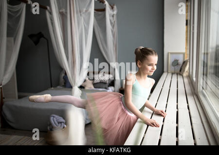 Cute little ballerina in pink ballet costume and pointe shoes is dancing in the room. Child girl is studying ballet. - Stock Photo