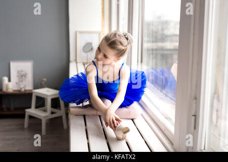 little girl dreams of becoming a ballerina. Child girl in a blue ballet costume dancing in a room. - Stock Photo