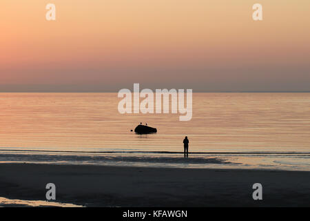 A silhouette of a solitary woman standing at the shore while sun sets over the horizon at Skaket Beach on Cape Cod - Stock Photo