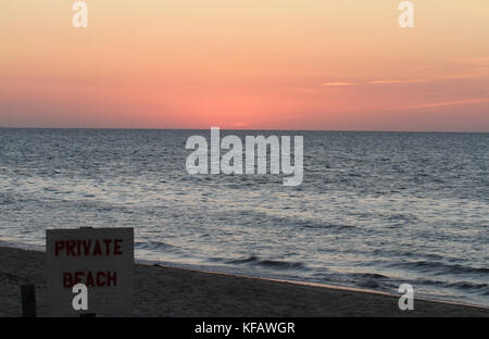 Sunset on Cape Cod Bay at Linnell Landing Beach, Brewster, Massachusetts, with posted 'Private Beach' sign in the - Stock Photo