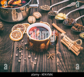 mulled wine in a brown cup and ingredients for making a drink, vintage toning - Stock Photo