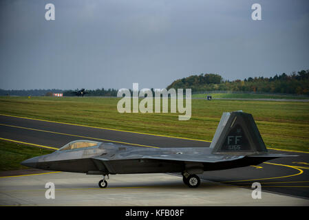 A U.S. Air Force F-22 Raptor stealth tactical fighter aircraft taxis on the runway at the Spangdahlem Air Base October - Stock Photo