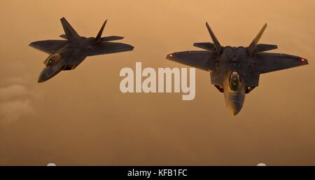 Two U.S. Air Force F-22 Raptor stealth tactical fighter aircraft fly in formation at sunset August 21, 2012 over - Stock Photo