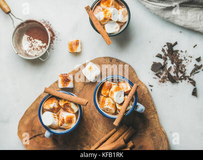 Hot chocolate in enamel mugs with cinnamon and roasted marshmallows over grey marble background, top view - Stock Photo
