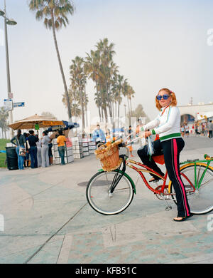 USA, California, Los Angeles, Venice Beach, a hip young woman strikes a pose with her bike on the Venice Beach Boardwalk - Stock Photo