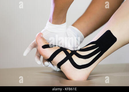 doctor physiotherapist with gloves applying kinesio medical taping on the left ankle of a patient caucasian woman - Stock Photo