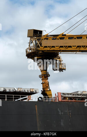 Machinery loading coal into the hold of a ship ready for shipping to customers around the world from Australia. - Stock Photo