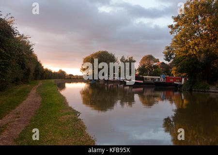 narrowboats and towpath along Cooks Wharf at sunset, Grand Union Canal Outer Aylesbury Ring, Cheddington, Buckinghamshire, - Stock Photo